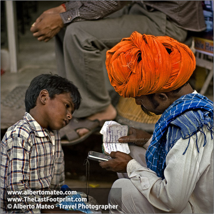 Father and son consulting agenda, Pushkar Camel Fair, Rajastan, India. | Cropped detail.