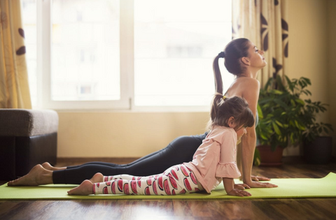 Mom daughter duo doing yoga at home during quarantine