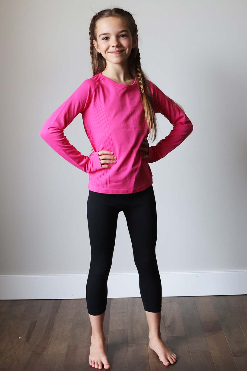 young girl with braids smiling with her hands on her hips wearing a purple long sleeve top and black athletic capris leggings