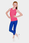 young redhead girl smiling while wearing a pink tank top and blue athletic capris leggings