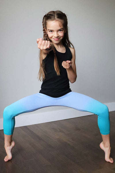 young girl on tip toes posing while wearing limeapple's turquoise athletic capris leggings inside a studio