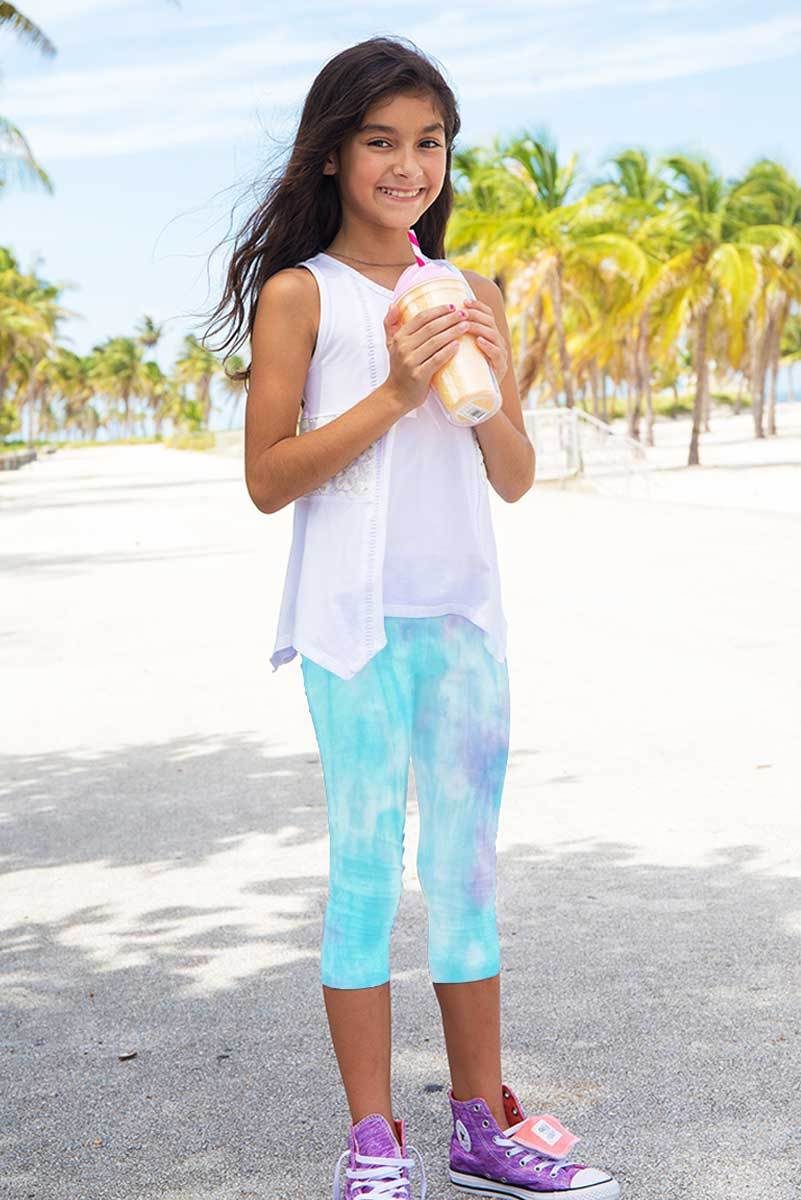 young girl smiling while holding a smoothie and wearing light turquoise capris leggings on the beach