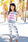 brunette tween smiling while wearing limeapple's grey tie dye shirt and grey tie dye leggings behind palm trees