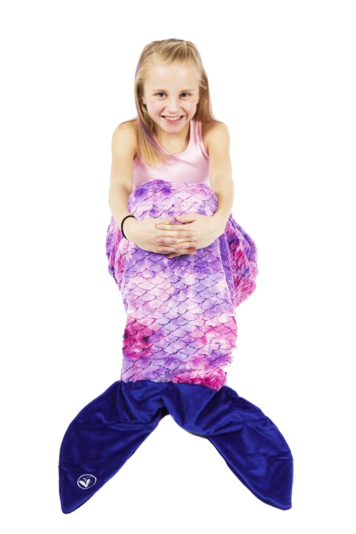 blonde girl smiling and sitting down in limeapple's purple tie dye mermaid tail sleeping bag