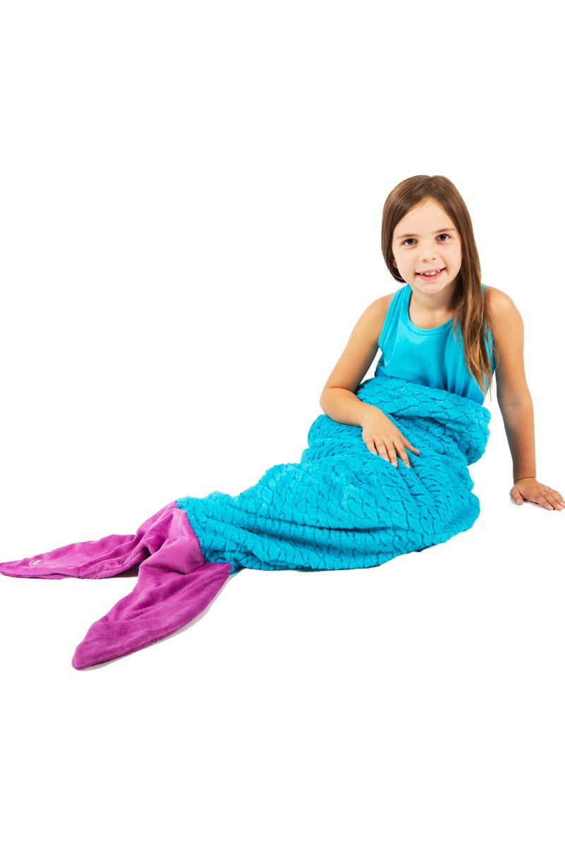 brunette girl smiling while sitting down in limeapple's turquoise mermaid tail sleeping bag