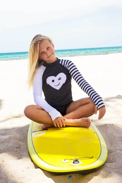 Young girl wearing Limeapple's kimia rash guard swimsuit set sitting on a yellow surfboard