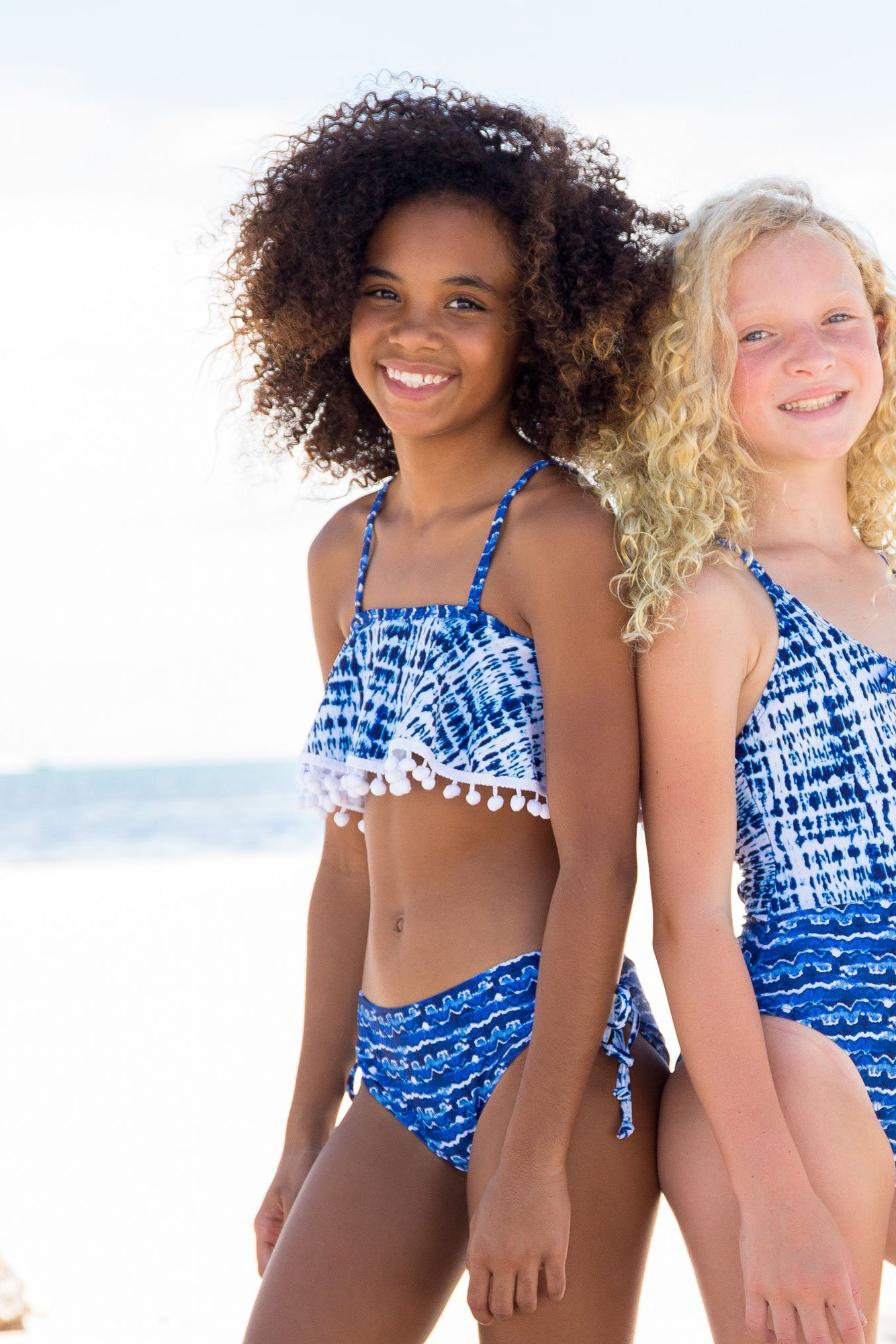 two young girls wearing limeapple's liset blue watercolor ruffle bikinis on the beach