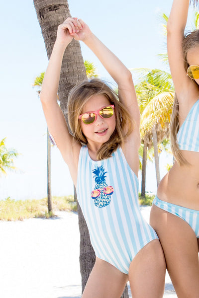 Young girl with sunglasses wearing limeapple's liza pineapple print one piece swimsuit behind palm trees