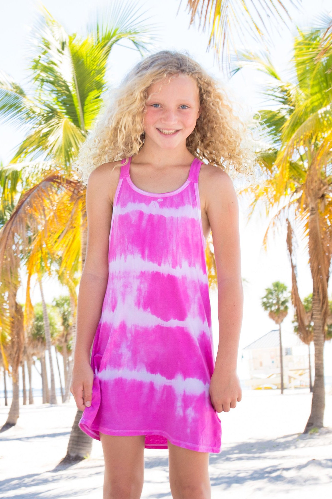 Tween blonde girl wearing a pink tie dye swim cover up dress behind palm trees