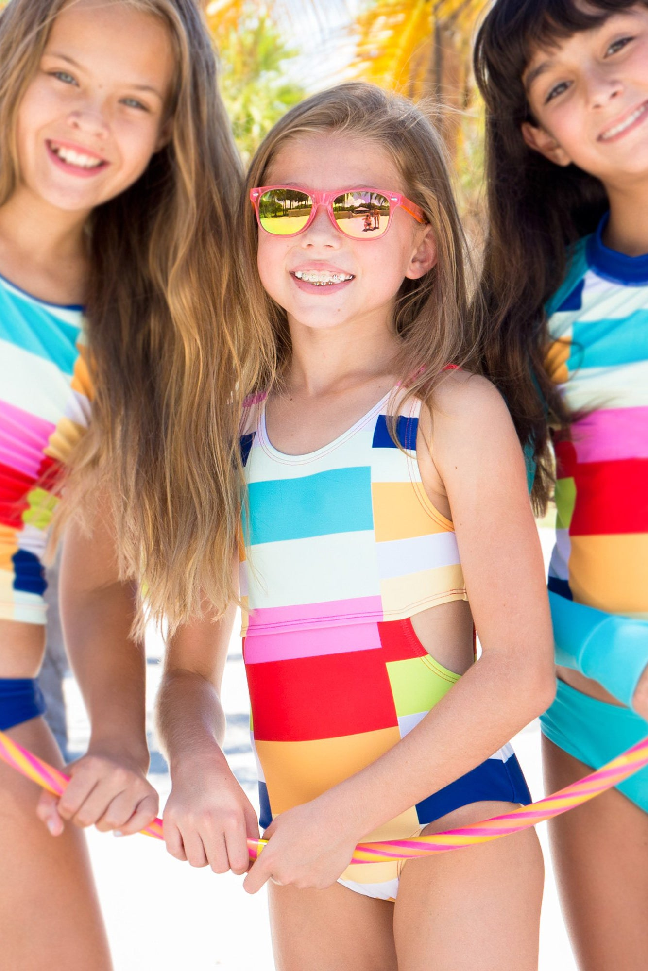three young girls wearing color block one piece swimsuits behind palm trees