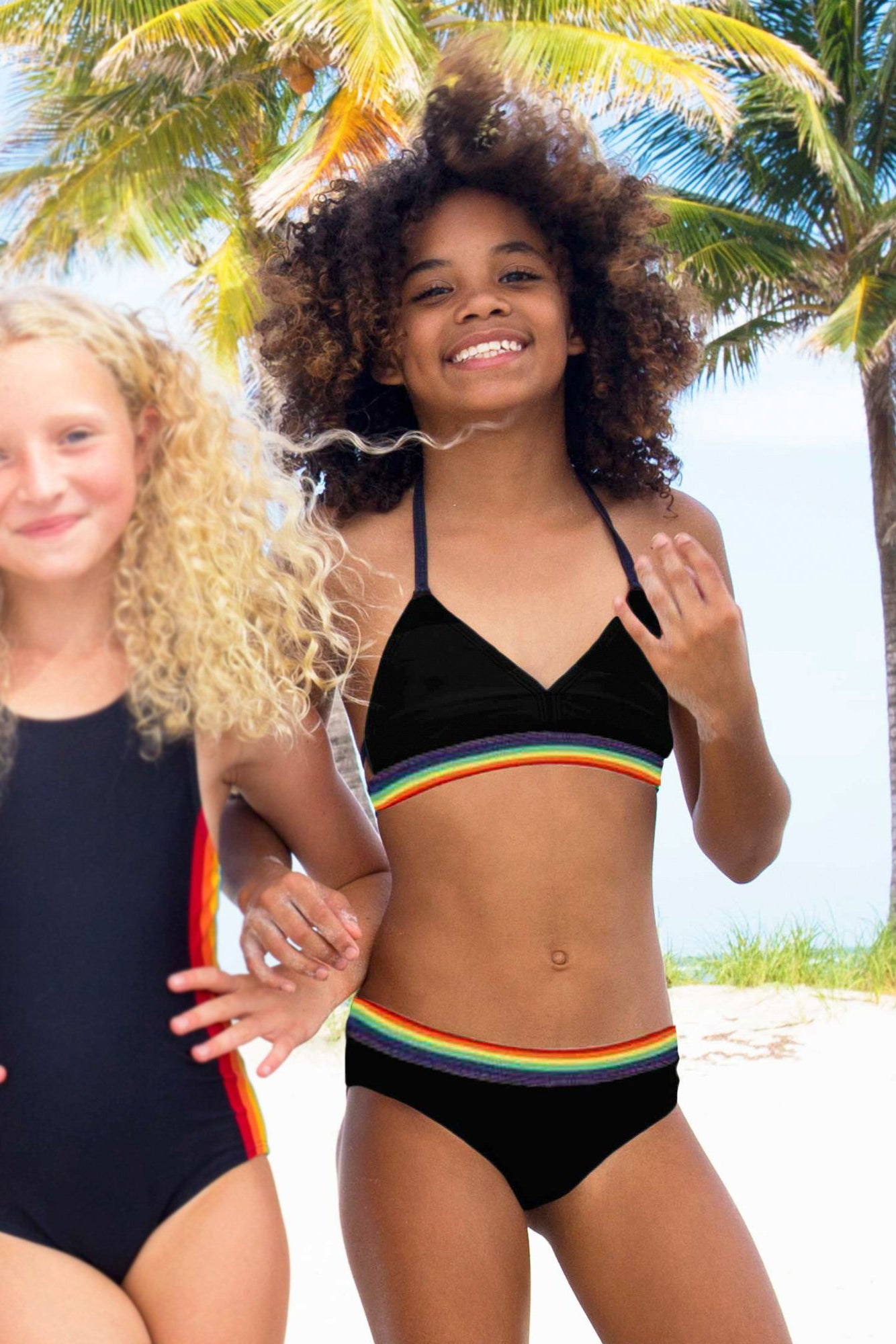 girl wearing limeapple's rainbow band black two piece bikini on the beach with another girl