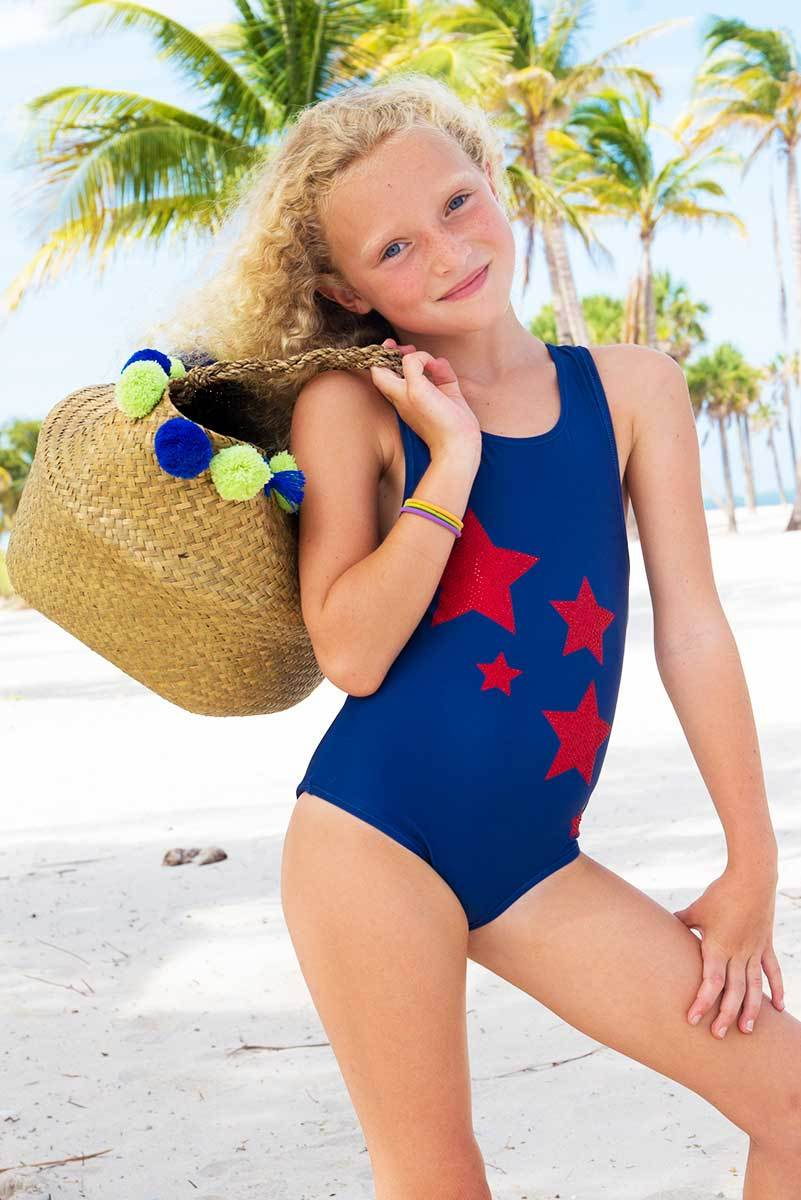 young blonde girl wearing limeapple's red rhinestone star blue one piece swimsuit while holding a basket and smiling