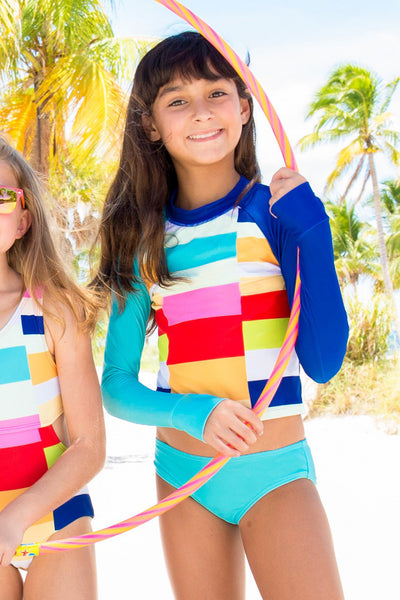 young girl wearing limeapple's colorblock rash guard set while holding a hula hoop on the beach behind palm trees