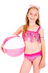blonde girl holding a pink & white striped beach ball smiling while wearing limeapple's pink fringe bikini
