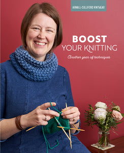 Boost Your Knitting cover image features a red background and a woman wearing a blue dress knitting a green mitten on double-pointed needles, she is also wearing a blue tuck stitch cowl