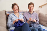 Jen and Jim Arnall-Culliford sitting on the sofa, ready to help you to Boost Your Knitting