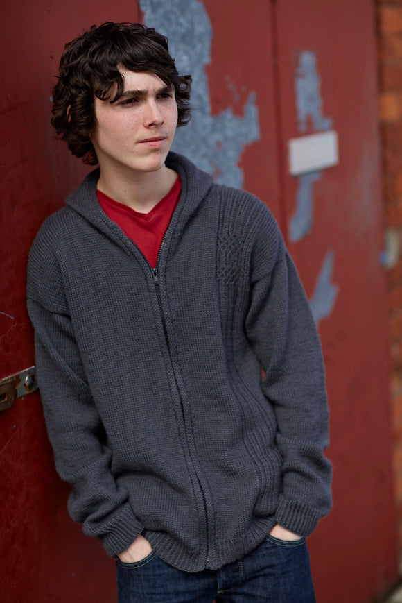 A young man wears the Bruton Hoody, leaning against a red door.
