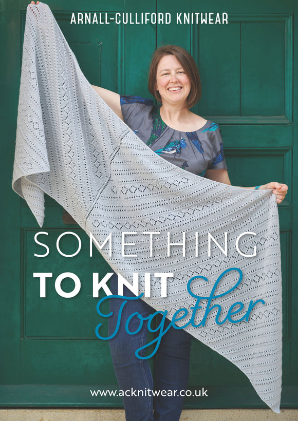 Cover image showing Jen standing in front of a green door, holding a large grey rectangular shawl. The shawl has diagonal bands of texture and lace patterning and an icord edging. Over the image are the words Arnall-Culliford Knitwear, Something to Knit Together and www.acknitwear.co.uk