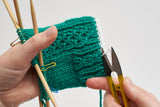 A sample photo from a tutorial showing waste yarn being removed from the cuff of a project