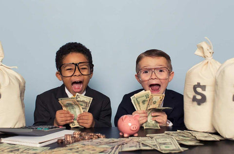two kids with money sitting at a desk