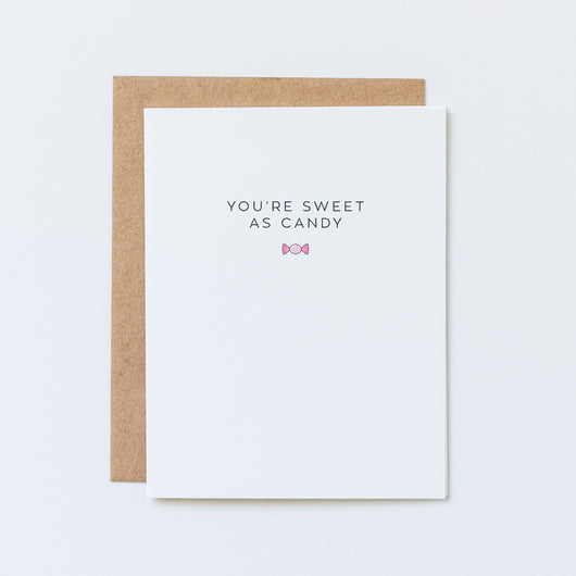 sweet as candy thinking of you card by aqua birch depicts a small hand designed pink wrapped candy icon on a minimalistic white surface, paired with a brown kraft envelope