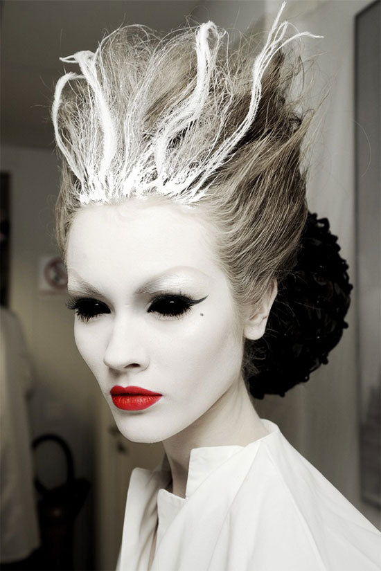 "For a more high-fashion Halloween, consider this ""bride-of-Frankenstein"" look. White face paint, red lips, and some spray-on hair color make for an easy transformation."