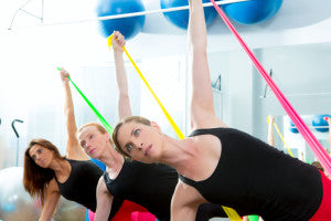 Aerobics pilates women group with esistance bands in a row at fitness gym