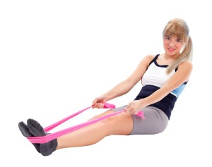 Pretty woman exercises with stretch band around her feet
