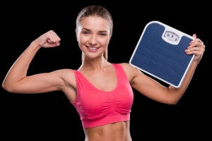 In perfect form. Sporty young woman holding weight scale and showing her bicep while standing against black background
