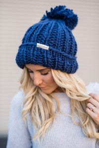 Blue knitted beanie with pom pom.