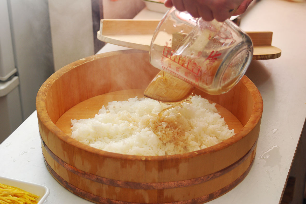 Once the rice is cooked, move it into a Handai and mix it with sushi vinegar.