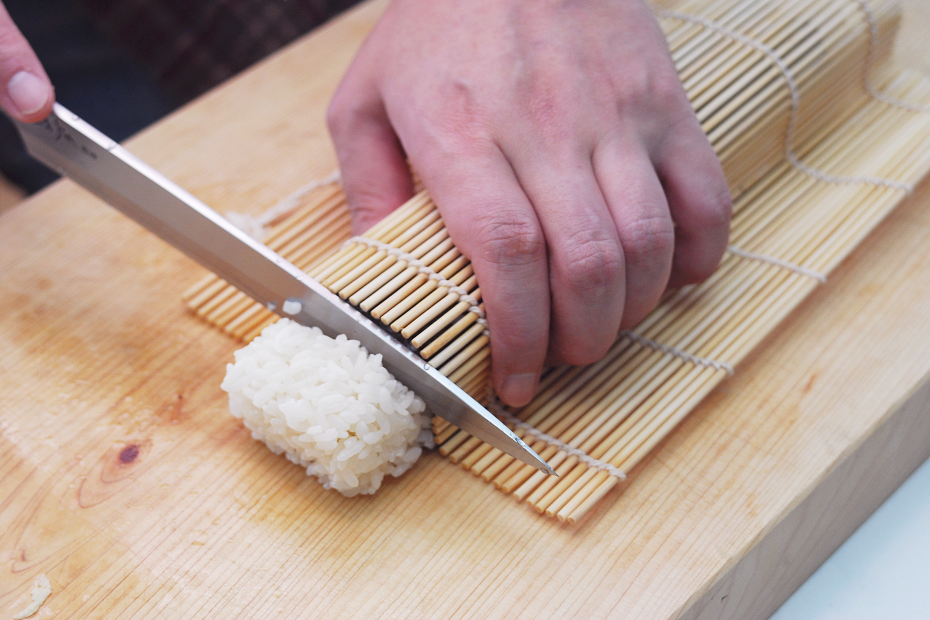 Cut off the both edges that are not wrapped with seaweed laver, and the cut the rest at even intervals.