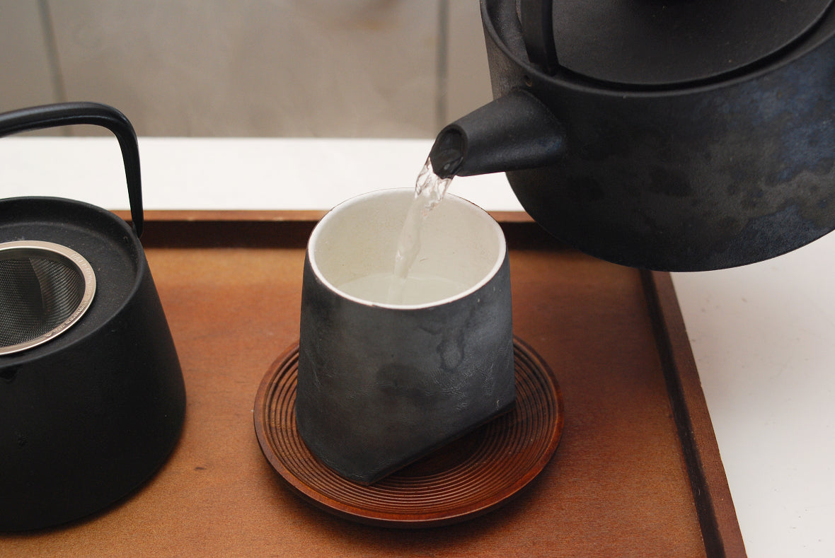 Pour hot water from Tetsubin to each teacup. This is to cool hot water and pre-warm teacups.