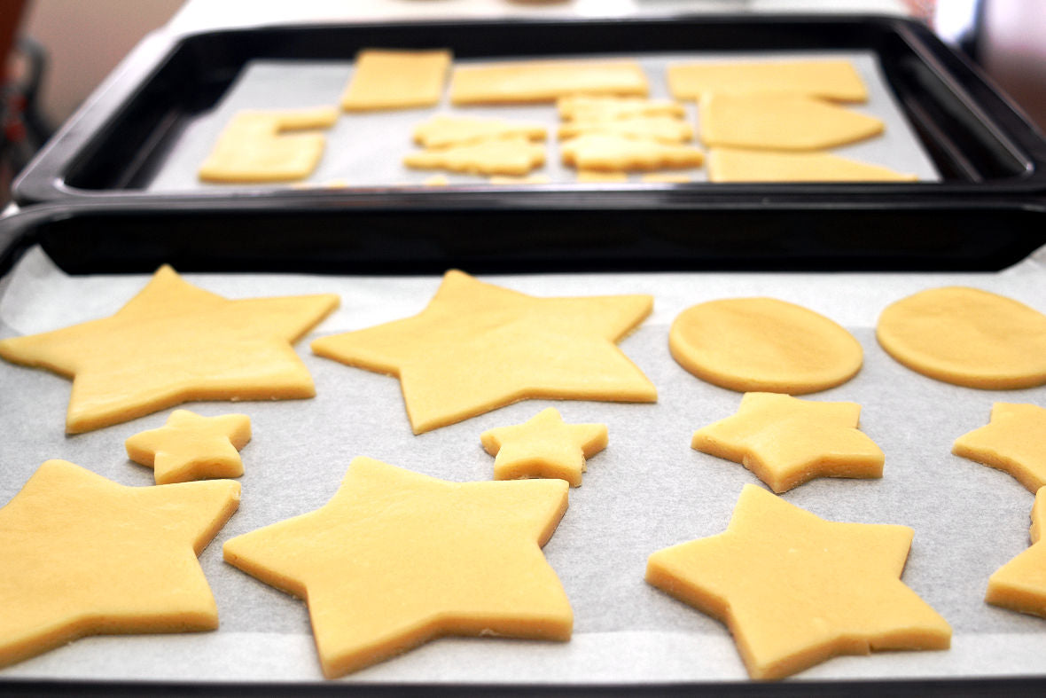 Once cut out all the shapes, place a sheet of parchment paper on the baking tray and lay each portion of dough on the tray.