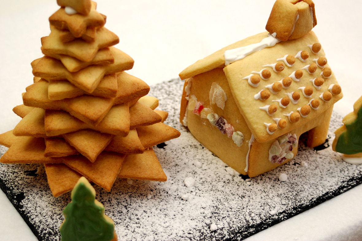 Sift powder sugar over the plate and lay out the cookie house and fir tree would enhance Christmas atmosphere.
