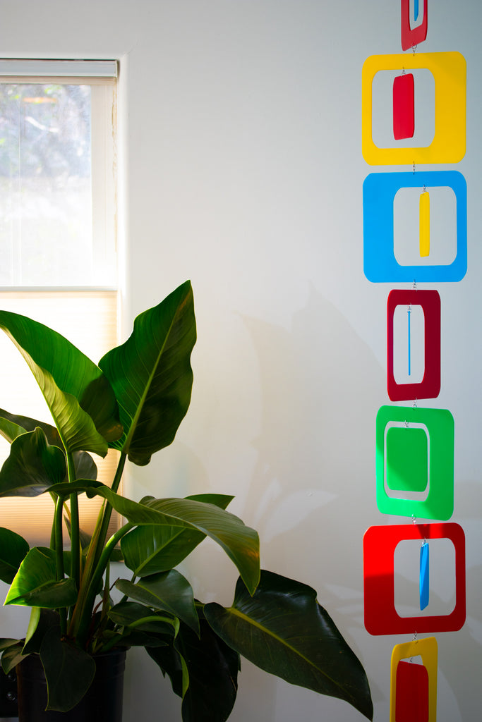 Colorful Vertical Mobile in red, yellow, green, and blue, with large plant next to window - atomicmobiles.com