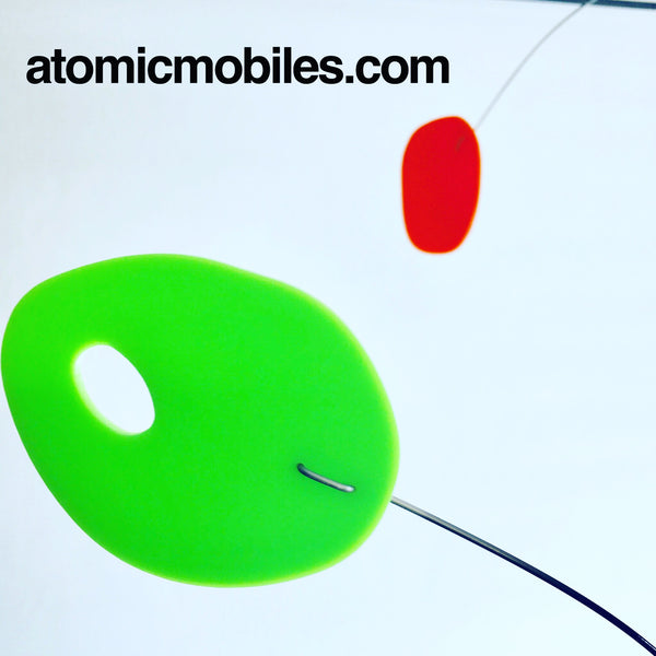 Closeup of MCM modern art mobile in lime green and orange by AtomicMobiles.com