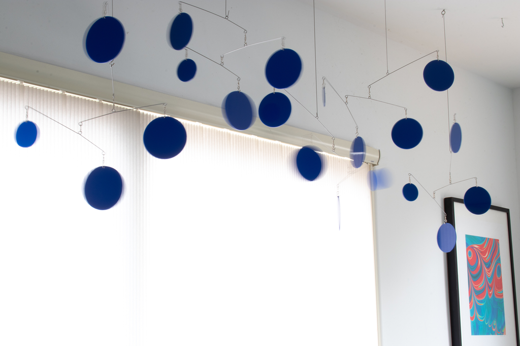 Spectacular navy blue large hanging art mobile in front of patio sliding door blinds in bedroom by AtomicMobiles.com