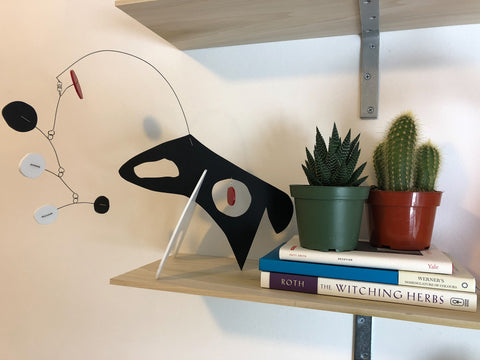 Modern art stabile sculpture - The Dog - by AtomicMobiles.com with books and succulent and cactus plants