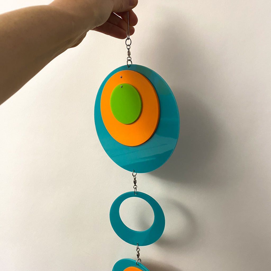 Holding the beautiful Palm Springs Wall Art Mobile in Aqua Blue, Orange, and Lime Green by AtomicMobiles.com