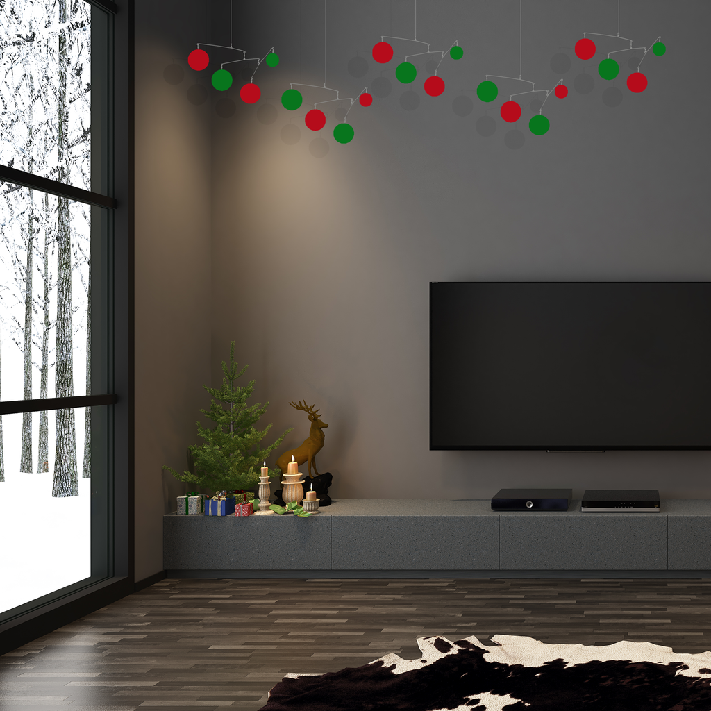 4 beautiful red and green hanging art mobiles in dark gray room with Christmas decorations and large TV with snow outside - mobiles by AtomicMobiles.com