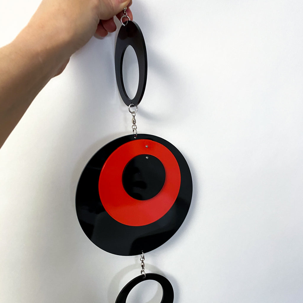 Holding the POPdots in black and red closeup - wall art mobiles by atomicmobiles.com
