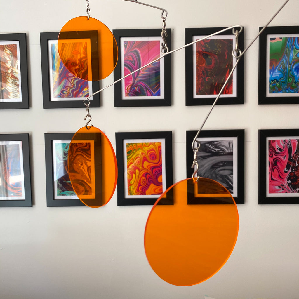 Clear Orange Acrylic Atomic Mobiles in front of MiniMOD abstract colorful art prints by AtomicMobiles.com
