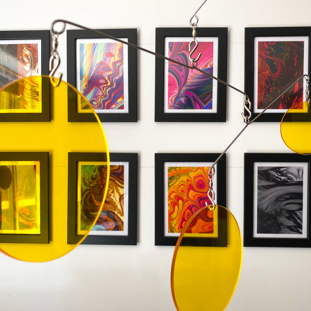 Clear Yellow Acrylic Atomic Mobiles in front of MiniMOD abstract colorful art prints by AtomicMobiles.com