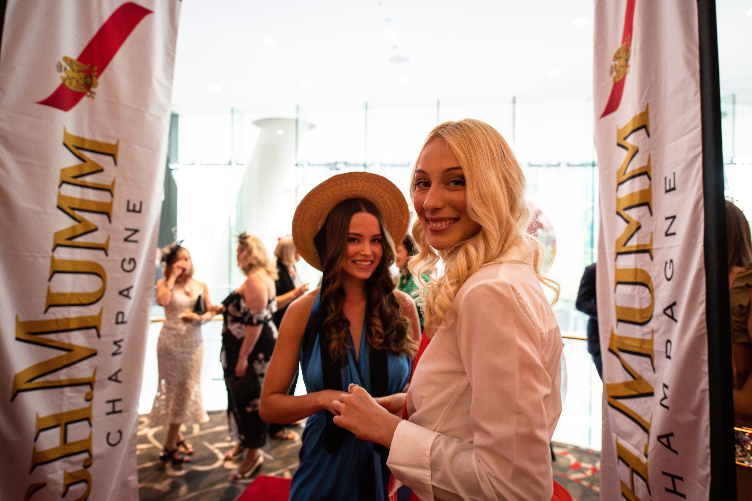Models at Melbourne Cup event smile at camera wearing Robe resort wear