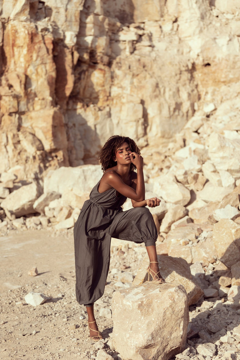 Woman poses while modelling for Australian fashion brand Robe, wearing The Sarah J jumpsuit in a Queensland sandstone quarry