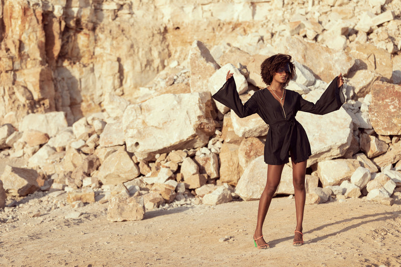 Woman lifts arms, standing in Queensland sandstone quarry modelling The Isabelle mini dress by Robe resort wear for women