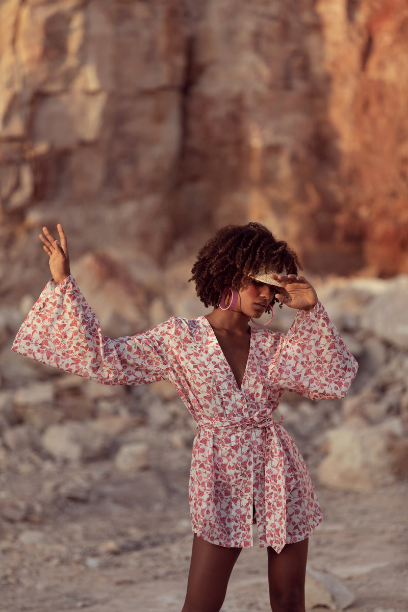 Model dances in Queensland sandstone quarry, wearing the Isabelle in floral print English Rose by Robe resort wear for women