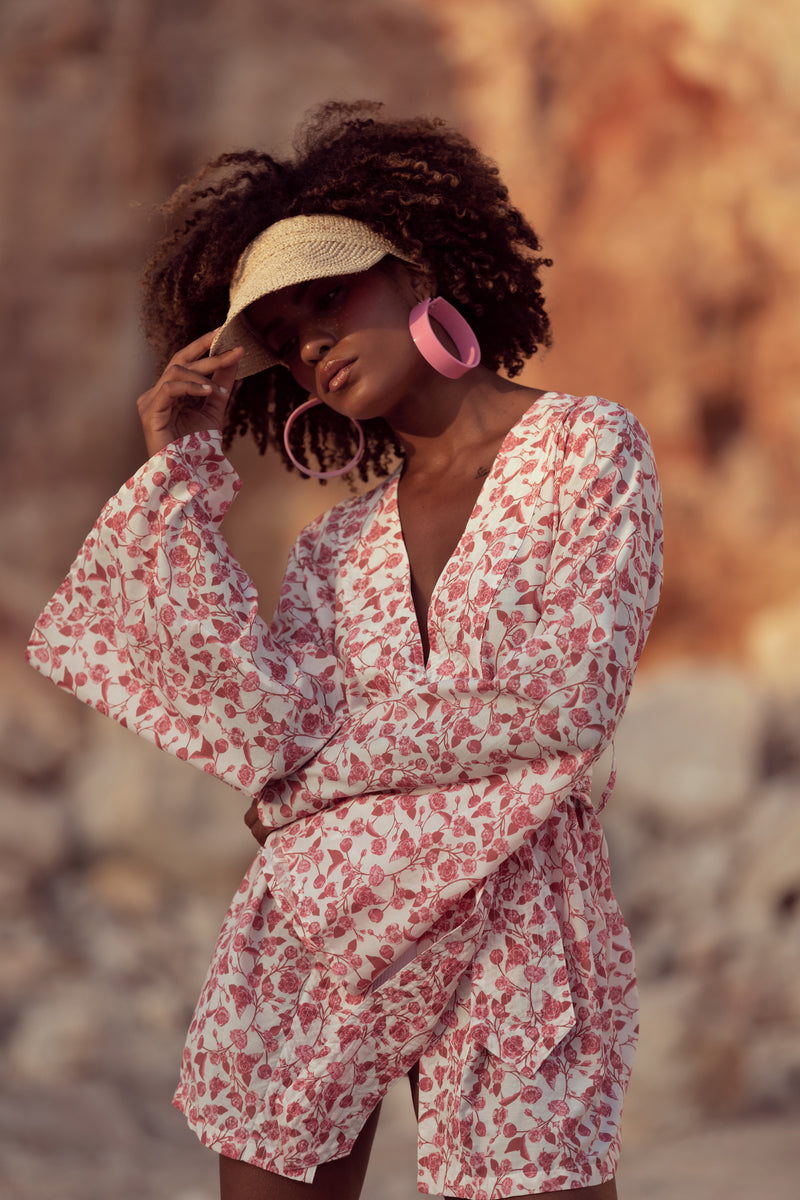 Model holds visor hat, wearing pink earrings and floral dress by Robe resort wear for women