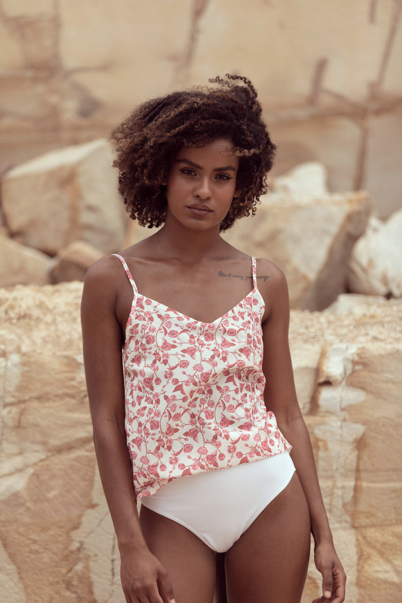 Model looks at camera, wearing white bikini bottoms and camisole singlet in floral print by Robe resort wear: The Camille in English Rose